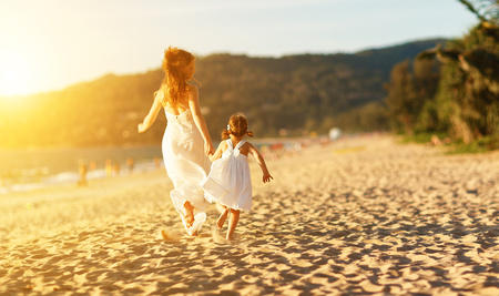 happy family at beach. mother and child daughter run, laugh and play at sunset